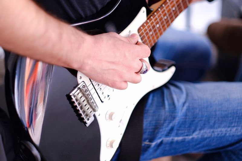 Midsection Arts Culture And Entertainment One Person Music Guitar Musical Instrument Musical Equipment Leisure Activity Focus On Foreground Lifestyles Playing Hand Plucking An Instrument String Instrument Human Hand Jeans
