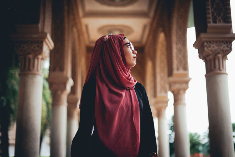 Low Angle View Of Young Woman Wearing Hijab Standing In Temple