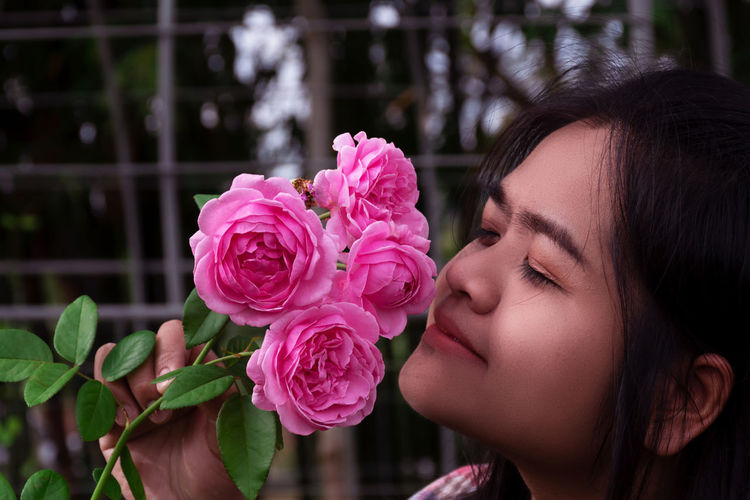 Women are smelling Bishops Castle rose in the garden happily. Adult Aroma Asian Woman Attractive Background Beautiful Beauty Bishops Castle Blossom Color Colorful Cute Day Delivery Face Female Floral Flower Fragrance Garden Gardening Girl Green Happily Happy Holiday Lady Model Nature One Park People person Pink Plant Portrait Pretty Red Romance Rosé Roses Smell Smiling Spring Summer Sunlight White Woman Women Young Flowering Plant Headshot One Person Vulnerability  Beauty In Nature Freshness Close-up Real People Fragility Leisure Activity Lifestyles Pink Color Flower Head Inflorescence Focus On Foreground Rose - Flower Outdoors Human Face Beautiful Woman Teenager