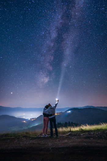 Rear view of couple standing on field against sky at night