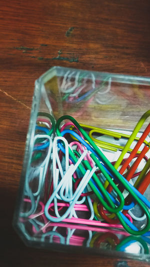Close-up of multi colored paper clips in container at table
