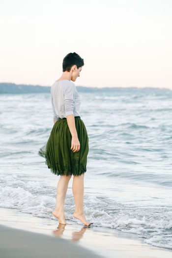 Full length of woman standing on shore at beach