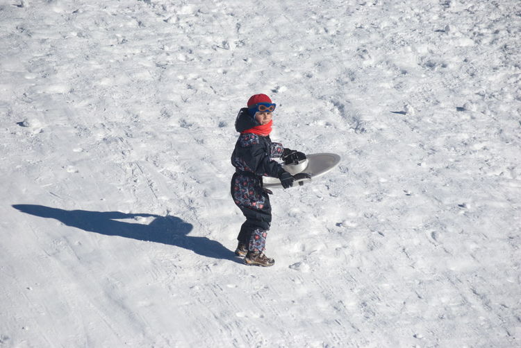 High angle view of boy with sled walking on snow