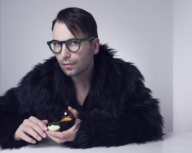 Portrait Of Man Wearing Fur Coat Against White Background