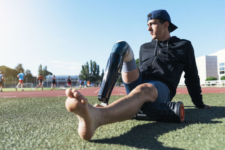 Young athlete with prosthetic leg relaxing at sports track
