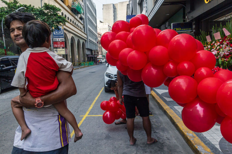 Rear view of couple holding balloons at city