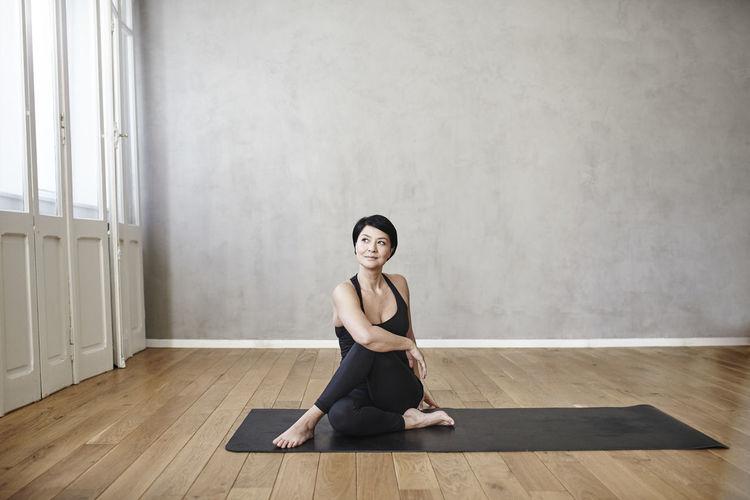 Full length of woman sitting on hardwood floor