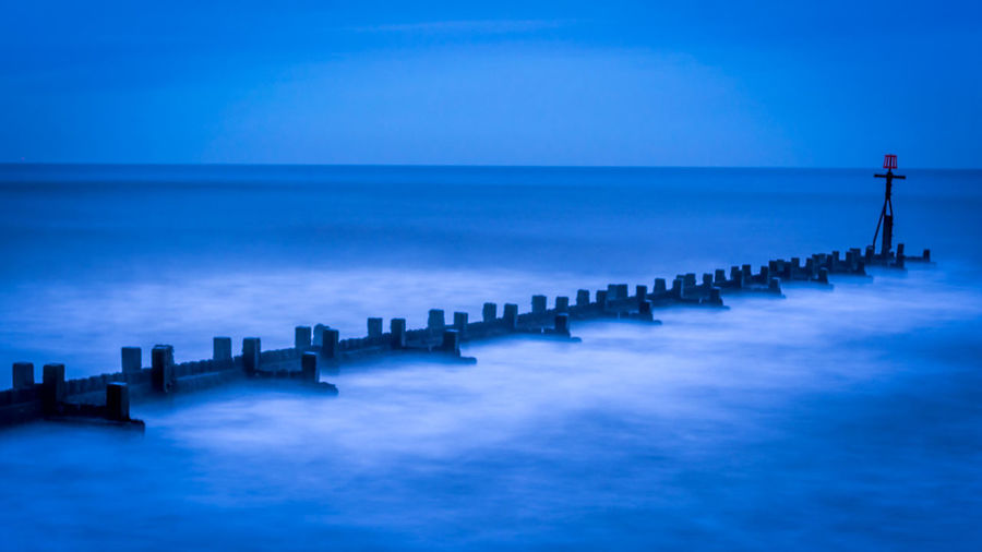 Wooden posts in sea against blue sky