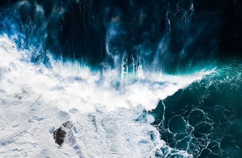 Aerial view of waves breaking against the coast