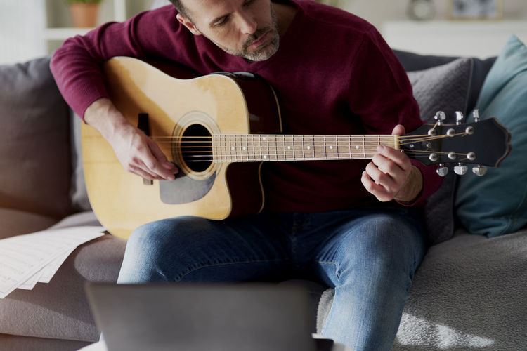 Midsection of man playing guitar on sofa at home