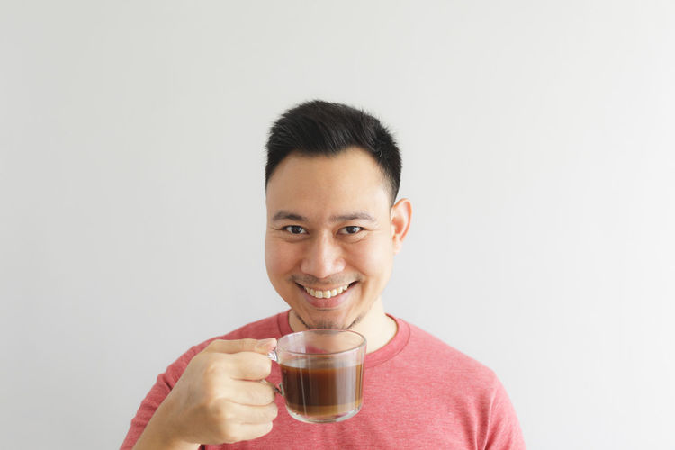 Portrait of a smiling young man drinking glass against white background