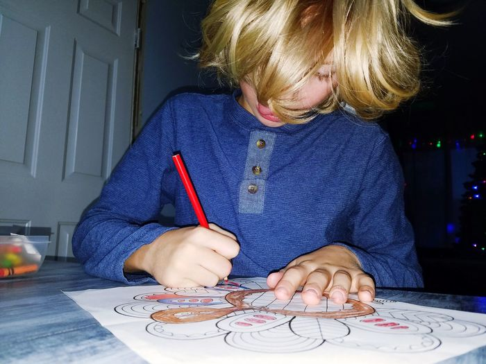 Close-up of boy drawing on paper at table in home