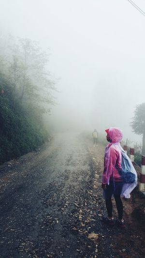 Rear view of woman standing in foggy weather