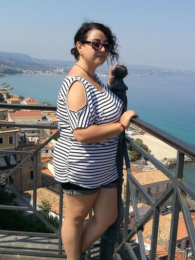 Woman wearing eyeglasses while standing by railing during sunny day