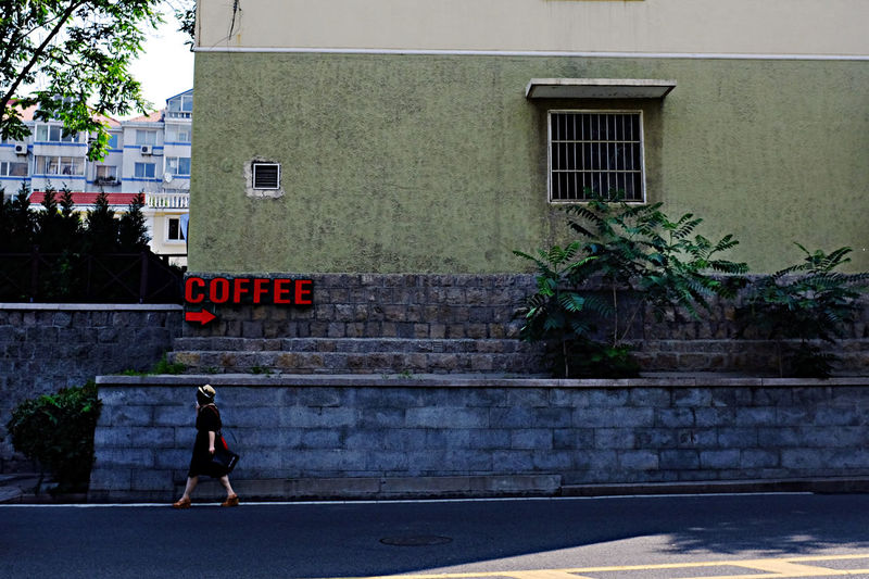 A woman walking through a coffee sign. 2016 EyeEm Awards China Coffee Leisure Activity Pedestrian Pedestrians Qingdao China Solitary Streetphotography Woman Fujifilm X100T Fujifilm People China 2016 Here Belongs To Me Street Color On The Way