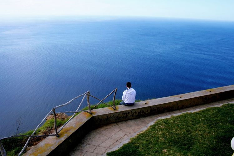 Rear view of man sitting on retaining wall against blue sea