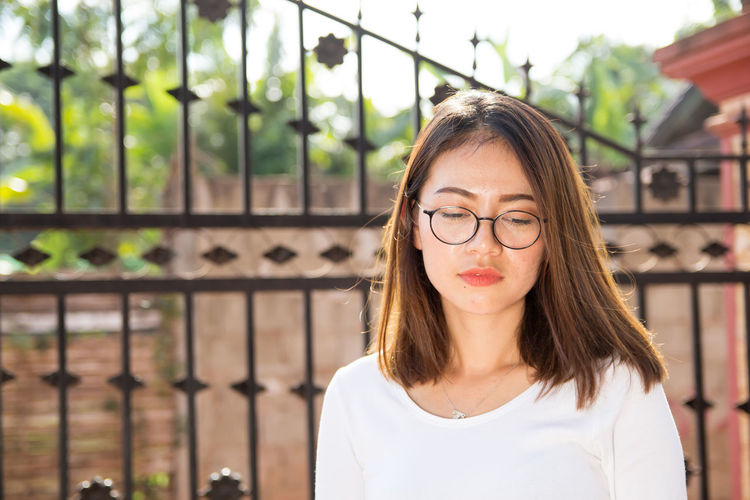 Young woman with brown hair wearing eyeglasses in city