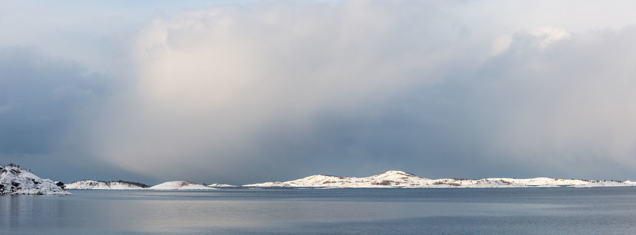 Group of islands ahead of Norway's second biggest island Senja  . Arctic Clouds Cold Dramatic Light Dramatic Sky Islands Landscape Mountain Range Northern Norway Ocean Panorama Panoramic Landscape Scenics Sea Season  Sky Snow Snowcapped Mountain Weather Winter Wintertime