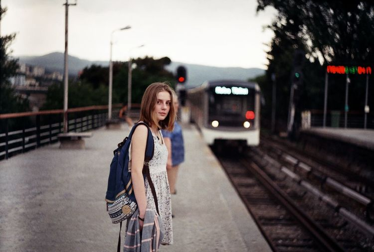 Woman on railroad station platform in city