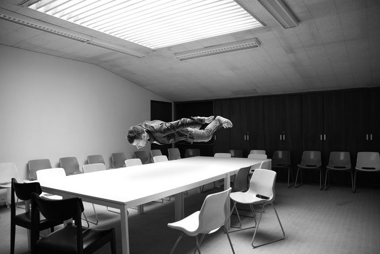Man levitating over table in conference room