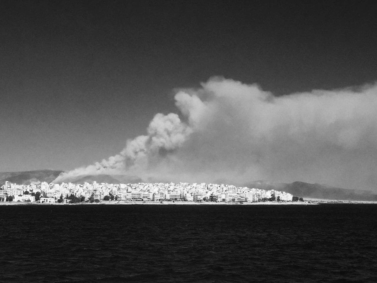 Smoke emitting from city by sea against sky