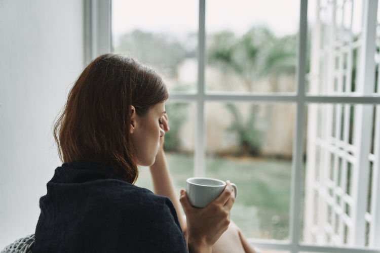 Depressed woman holding coffee cup sitting by window