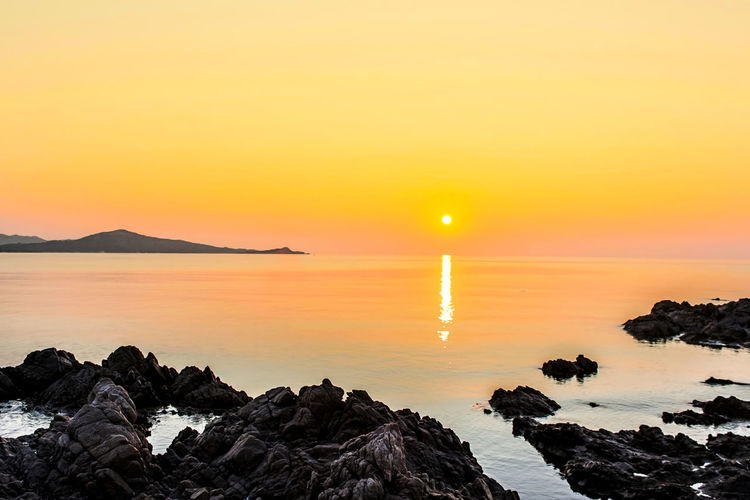 Scenic view of sea and rocky shore against orange sky