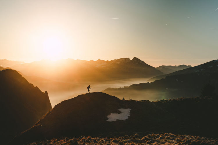Silhouette of a hiking person infront of sunset behind the Alps in Interlaken. Adventure Alpen Alps Beauty In Nature Discovery Fog Healthy Lifestyle Hiking Landscape Mountain Mountain Peak Mountain Range Nature One Person Outdoors People Scenics Silhouette Sky Sun Sunset Sunset_collection Switzerland Vacations Market Bestsellers 2017 Go Higher