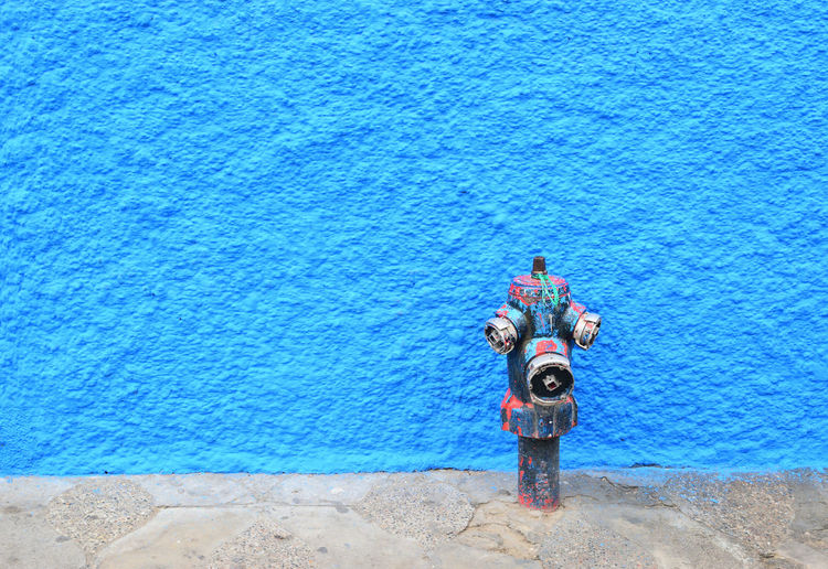 Fire hydrant against blue wall