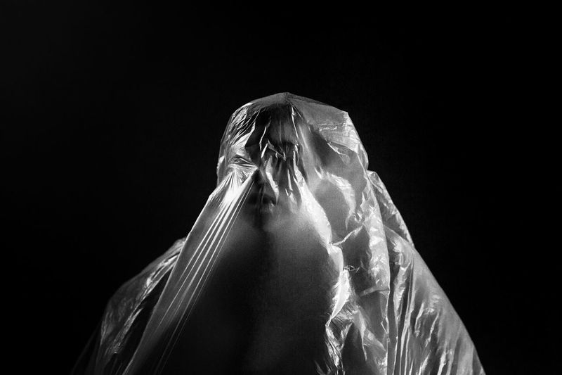 Person wrapped in plastic against black background