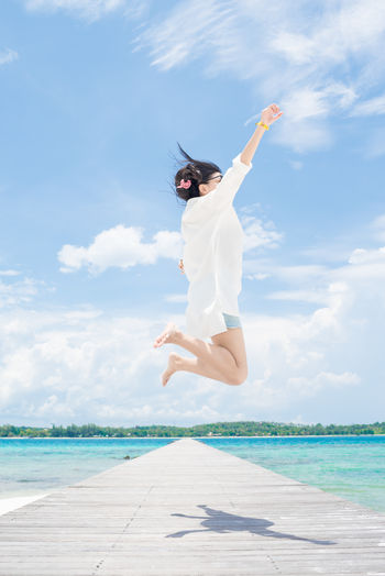 Low angle view of woman jumping over pier against sky