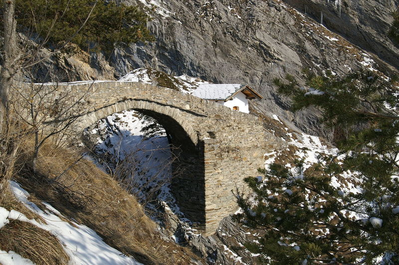 Side view of footbridge against snowed rocks