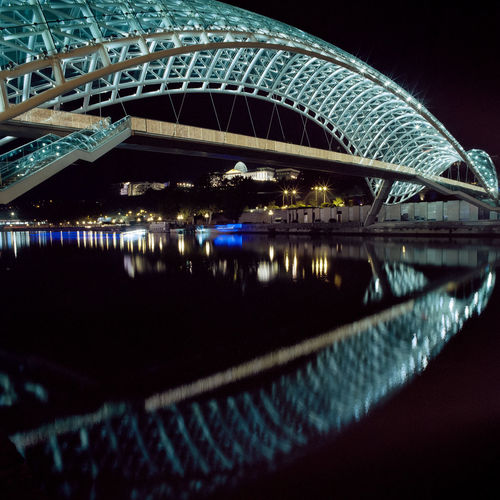 Illuminated bridge over river at night