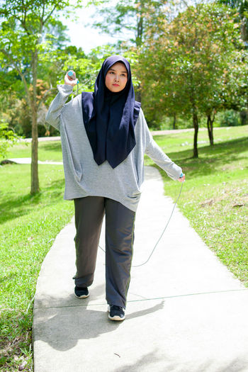 Full length portrait of woman standing on footpath