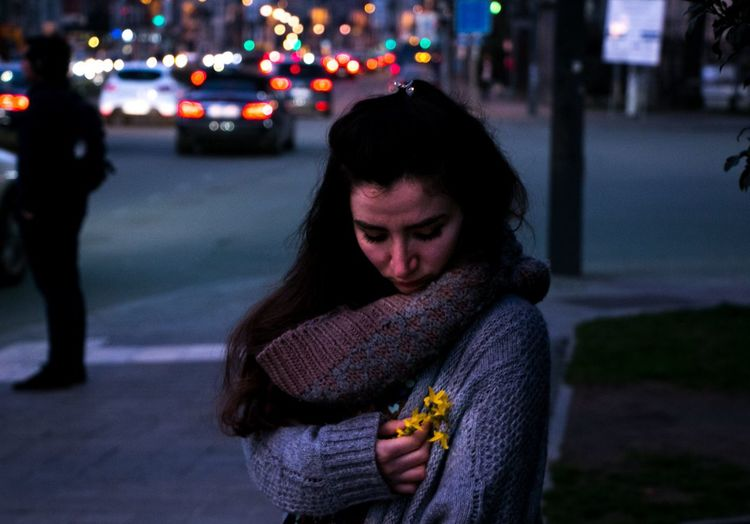 Woman Holding Flowers In City At Night