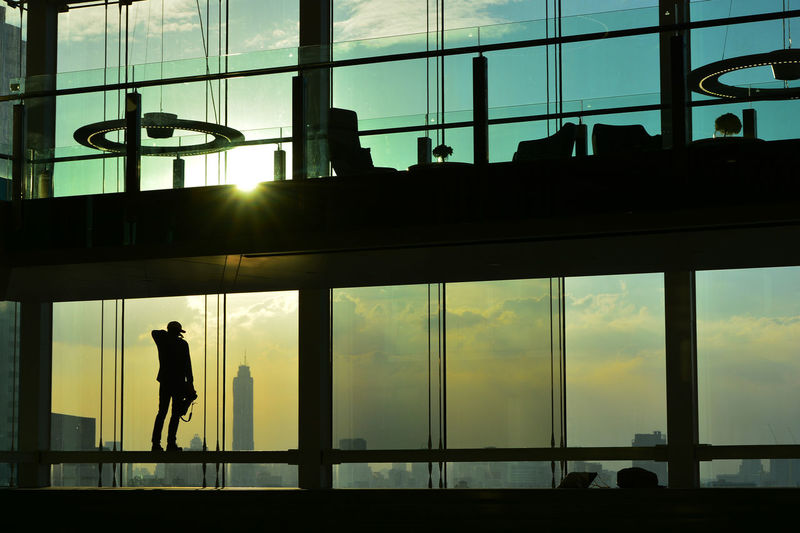 Silhouette man standing in modern building during sunset