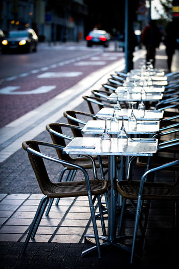 Seat In A Row Chair City Street Empty Table Focus On Foreground Absence Cafe Sunlight Transportation No People Day Restaurant Arrangement Business Mode Of Transportation Outdoors Order Waiting Cars Sidewalk Cafe Evening Gastronomy