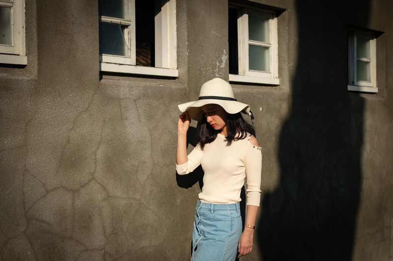 Woman wearing hat while standing by wall