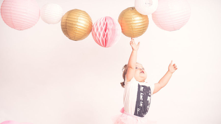 Low angle view of girl holding balloons against white background