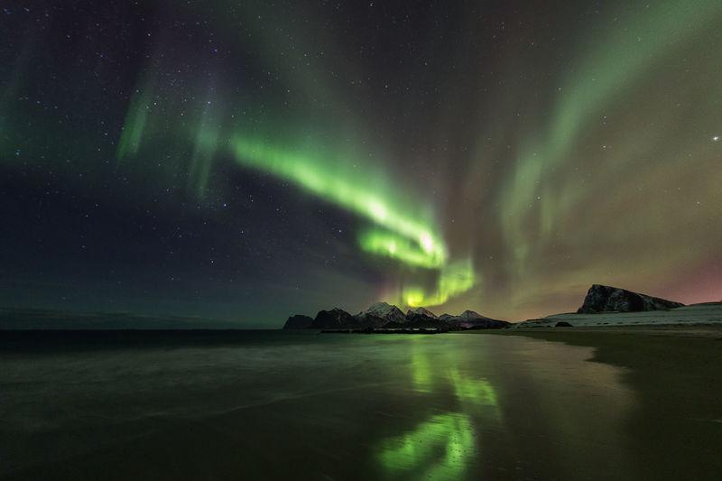 Scenic view of beach against aurora borealis at night