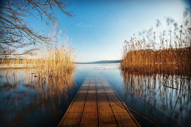 Pier amidst lake against sky