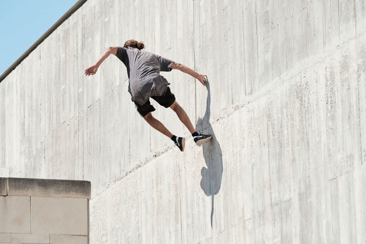 Rear view of man jumping against wall