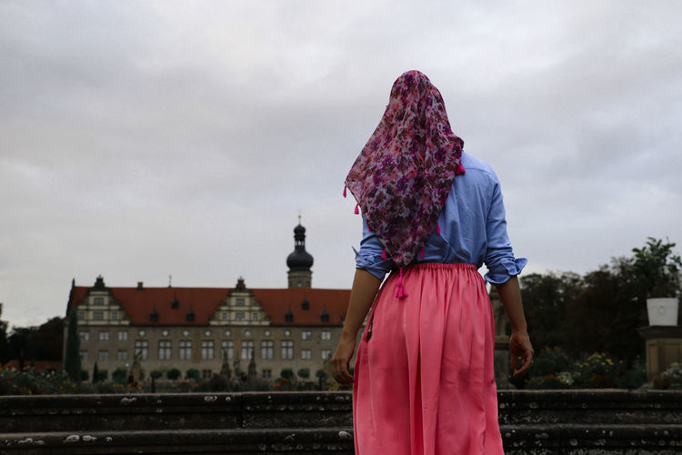 Rear view of woman standing against building and sky