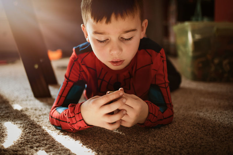 Boy looking at camera while sitting on mobile phone