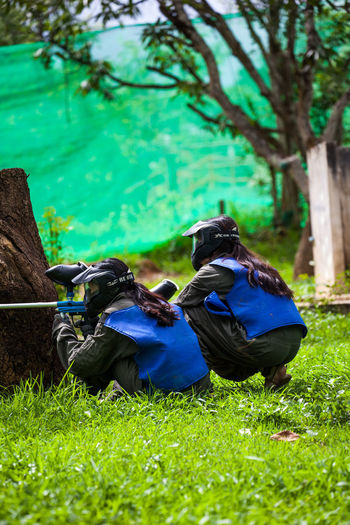 """Paintball is a competitive team shooting sport in which players eliminate opponents from play by hitting them with spherical dye-filled gelatin capsules (""""paintballs"""") that break upon impact. Paintballs are usually shot using a low-energy air weapon called a paintball marker that is powered by compressed air (nitrogen) or carbon dioxide. Paintball Childhood Day Extremsports Field Front Or Back Yard Full Length Grass Green Color Growth Land Leisure Activity Lying Down Men Nature Outdoors Paintball Team Park People Plant Real People Relaxation Sport Tree"""