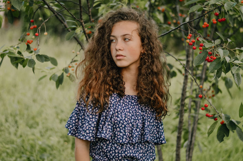 Portrait of teenage girl standing against plants