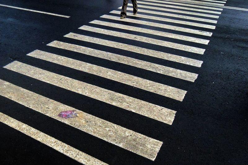 Low section of man walking on zebra crossing