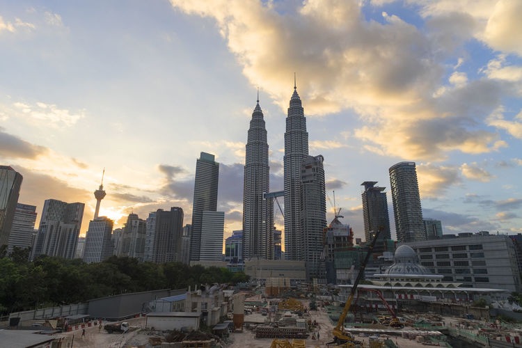 Petronas towers and skyscrapers against sky during sunset