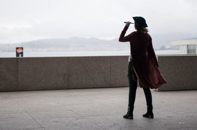 Rear view of woman looking through binoculars