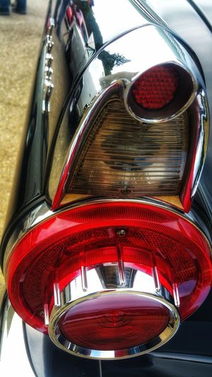 Vintage Tail light. Red! Tail Light Red Round Gold Chrome Silver  Signal Directional Vehicle Automobile Car Classic Antique Collector's Car Pattern Design Bold Timeless Angled Vintage Tail Light Red Close-up